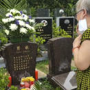 In this photo provided by Zhong Hanneng, she cries at the grave of her son, Peng Yi, during what would have been his 40th birthday at a cemetery in Wuhan in central China's Hubei province on Wednesday, Aug. 12, 2020. Peng first started coughing on Jan. 23 at the beginning of the coronavirus outbreak, but because of a shortage of test kits, he wasn't able to get tested for days. His first test result came out negative, barring him access to a hospital bed, and he wasn't able to be hospitalized until weeks later. By then his condition was critical, and he passed away on Feb. 19. (Courtesy Zhong Hanneng via AP)