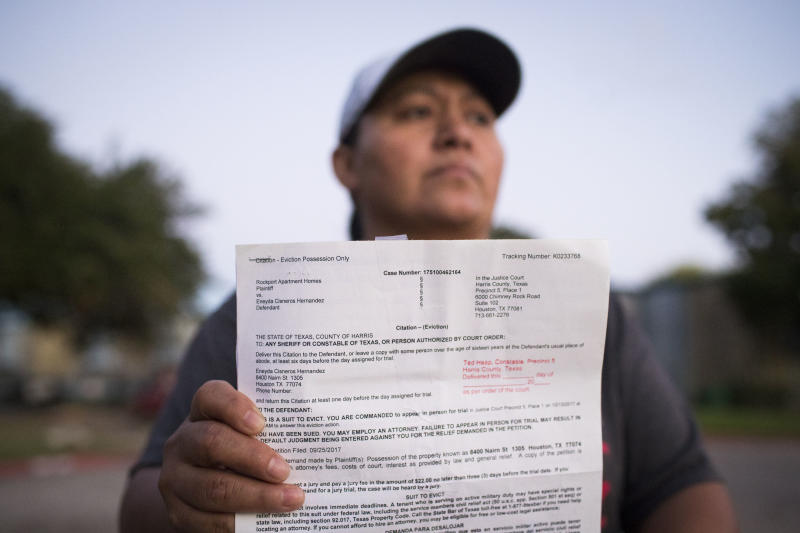 Eneyda Cisneros Hernandez holds an eviction citation she received from Rockport Apartments, the complex where she lives in Houston.  (Marie D. De Jesus/Houston Chronicle)