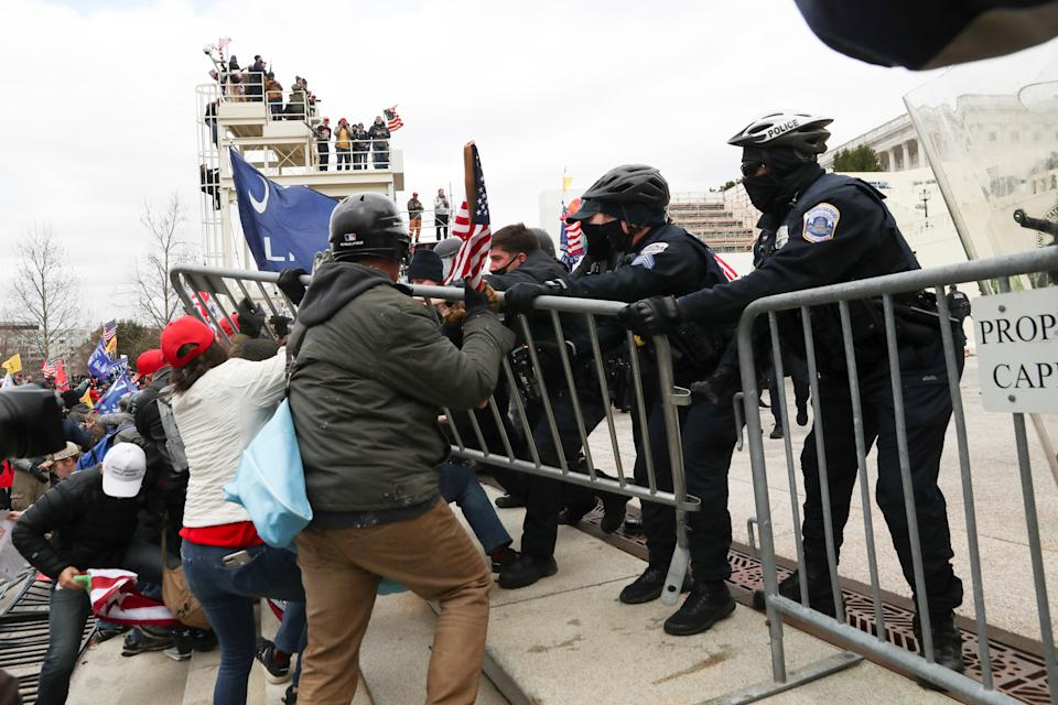Donald Trump supporters breach temporary fencing while clashing with police at the US Capitol building.
