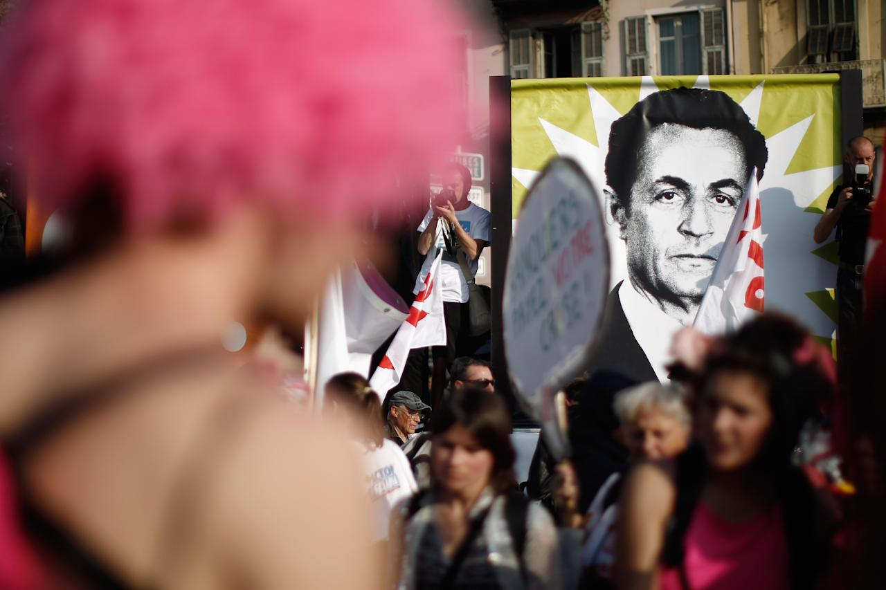 NICE, FRANCE - NOVEMBER 01:  A poster displaying the image of Nicolas Sarkozy is held aloft as thousands of demonstrators take part in an anti-G20 demonstration through the streets of Nice on November 1, 2011 in Nice, France. Anti-G20 demonstrators are gathered in Nice ahead of the arrival of the world's top economic leaders for the G20 summit in Cannes on November 3rd and 4th. The leaders are expected to debate current issues surrounding the global financial system in the hope of fending off a global recession and finding an answer to the Eurozone crisis.  (Photo by Christopher Furlong/Getty Images)