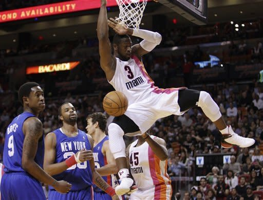 New Jersey Nets' MarShon Brooks (9) and Shelden Williams (33) watch as Miami Heat's Dwyane Wade dunks during the first half of an NBA basketball game in Miami, Tuesday, March 6, 2012. (AP Photo/J Pat Carter)