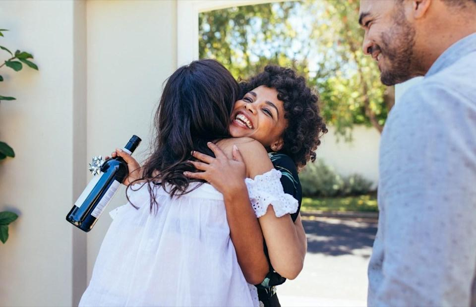 Woman greeting couple for having a new house. Smiling young woman with wine bottle congratulating her friend
