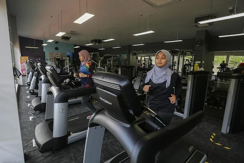 Dr Izzah Amirah Mohd Ahir (right) and Dr Shahdattul Mawarni Indahwan Shahputri Taib working out at Anytime Fitness in Shah Alam February 12, 2021. ― Picture by Yusof Mat Isa