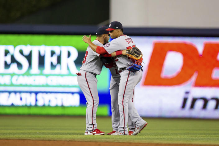 Washington Nationals left fielder Juan Soto (22) shares a hug with his fellow outfielders after defeating the Miami Marlins a baseball game on Thursday, June 24, 2021, in Miami.. (AP Photo/Mary Holt)