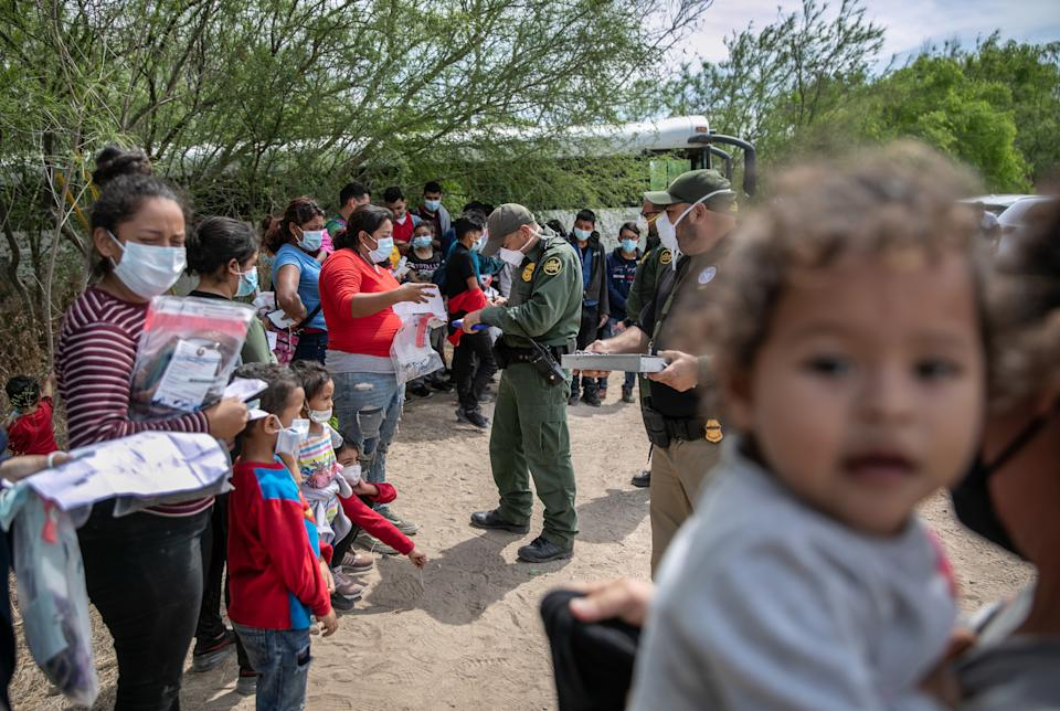 U.S. Border Patrol agents question a group of migrant families and unaccompanied children after they crossed the Rio Grande into Texas on March 25, 2021 in Hildago, Texas. (John Moore/Getty Images)