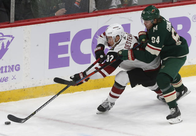 Minnesota Wild's Mikael Granlund, right, of Finland, tries to slow Arizona Coyotes' Jordan Oesterle during the first period of an NHL hockey game Tuesday, Nov. 27, 2018, in St. Paul, Minn. (AP Photo/Jim Mone)