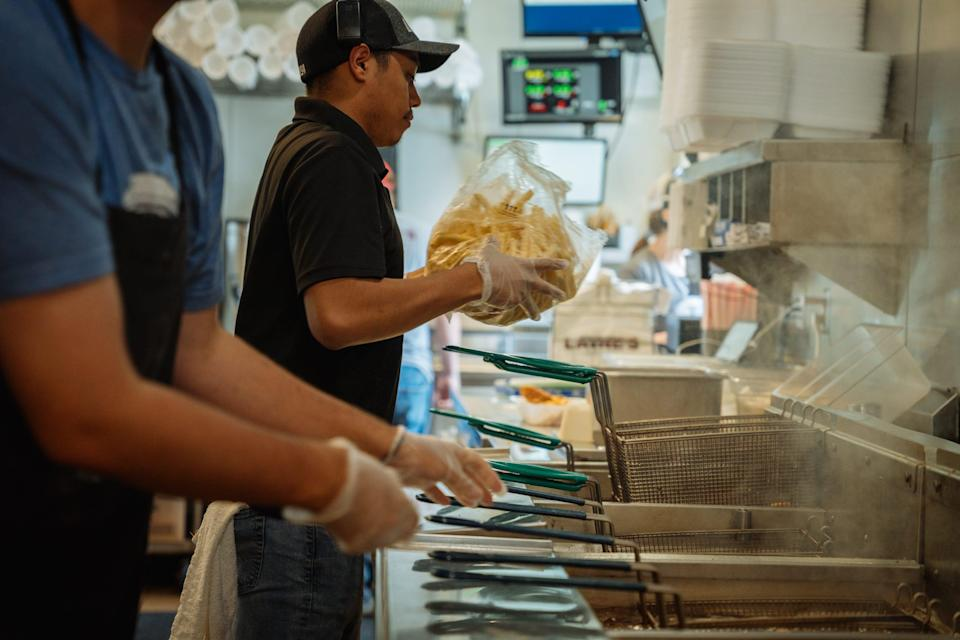 A fast-food worker prepares fries for the deep-fat fryer in a restaurant kitchen.