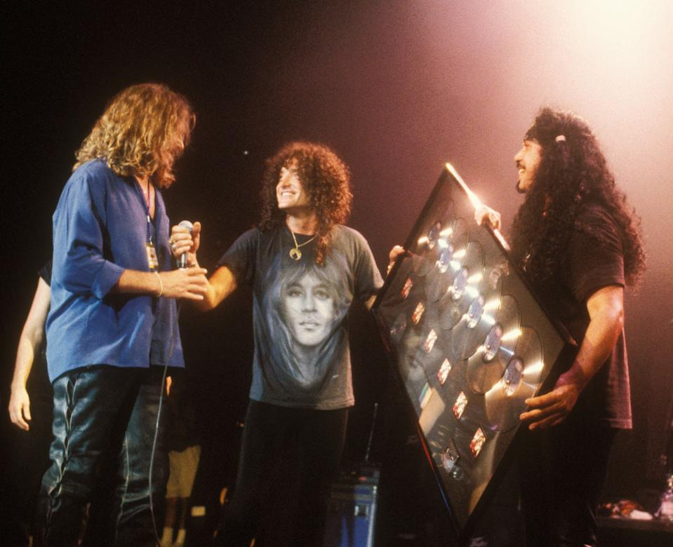 """Kevin DuBrow (C) and Frankie Banali (R) of Quiet Riot receive a mega-platnium album award for 6 million copies sold of their 1983 album """"Metal Health"""" while performing a live concert at the House of Blues Las Vegas on June 22, 1997 in Las Vegas, Nevada. (Photo by Annamaria DiSanto/WireImage)"""