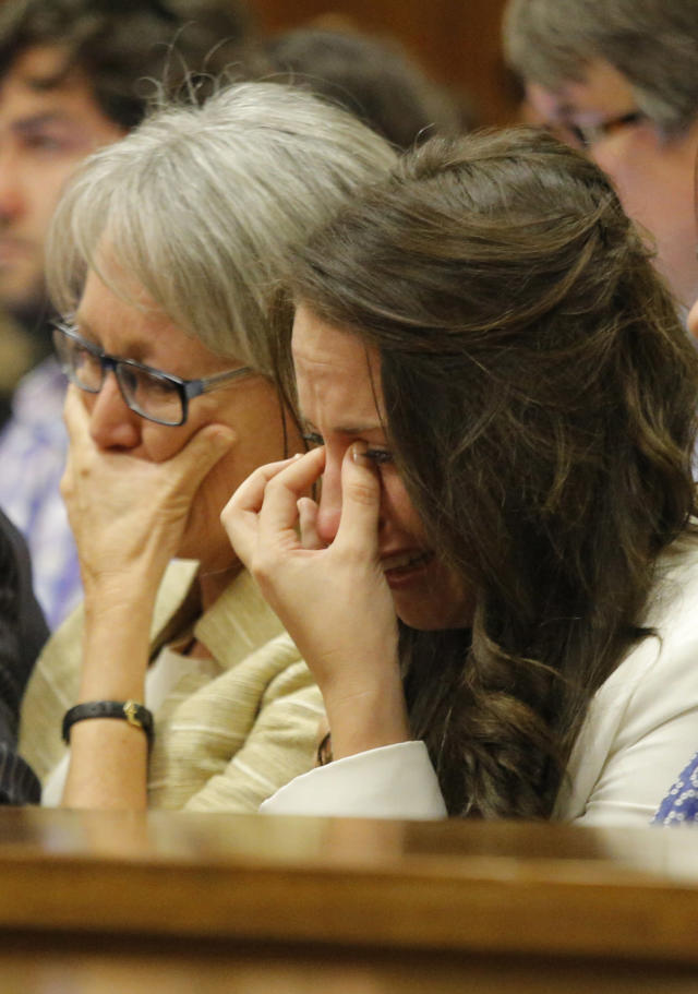 Sister of Oscar Pistorius, Aimee Pistorius, right, cries as she listens as her brother testifies in court in Pretoria, South Africa, Tuesday, April 8, 2014. Pistorius is charged with the murder of his girlfriend Reeva Steenkamp, on Valentines Day 2013. (AP Photo/Kim Ludbrook, Pool)
