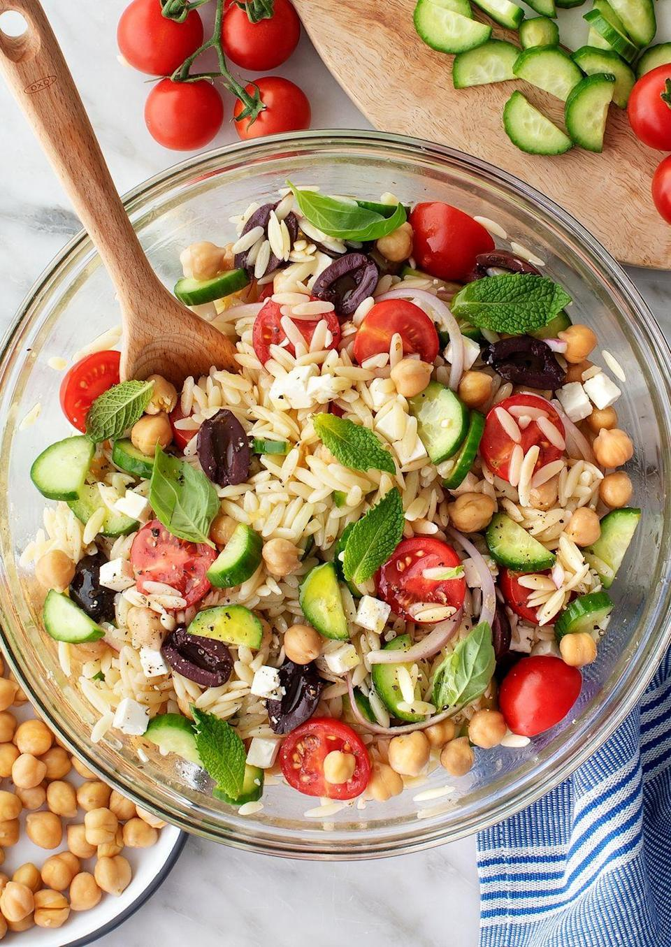 """<p>This grain-based salad is studded with tons of fresh flavor, thanks to summer garden staples like cucumbers, tomatoes, and basil. </p><p><a href=""""https://www.loveandlemons.com/orzo-salad/"""" rel=""""nofollow noopener"""" target=""""_blank"""" data-ylk=""""slk:Get the recipe."""" class=""""link rapid-noclick-resp"""">Get the recipe. </a></p>"""