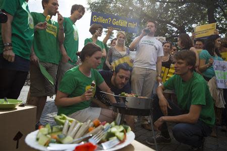 File photo of members of the Green Party, Die Gruenen, dressed in green T-shirts and eating ice cream as they watch a protest of members of the youth wing of the liberal Free Democratic Party (FDP) having a barbecue in front of the Green Party headquarters denouncing a proposed 'Veggie Day' in Berlin August 5, 2013. REUTERS/Thomas Peter/Files