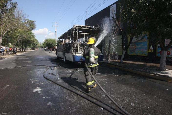 Firefighters spray a bus with water on Gomez Morin Avenue in Guadalajara, Jalisco state, Mexico, on May 1, 2015 (AFP Photo/Hector Guerrero)