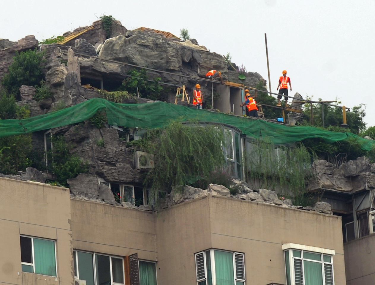 BEIJING, CHINA - AUGUST 16: (CHINA OUT) Workers begin to demolish a villa built privately on the rooftop of a 26-storey residential block on August 16, 2013 in Beijing, China. The owner Zhang Biqing said Wednesday that he will demolish the illegal building in 15 days following local bureau of city administration's decree. (Photo by ChinaFotoPress/ChinaFotoPress via Getty Images)