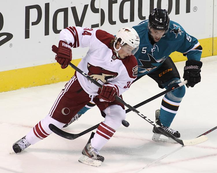 Phoenix Coyotes' Tim Kennedy (34) and San Jose Sharks' Jason Demers vie for the puck during the first period of an NHL preseason hockey game in San Jose, Calif., Saturday, Sept. 21, 2013. (AP Photo/Mathew Sumner)