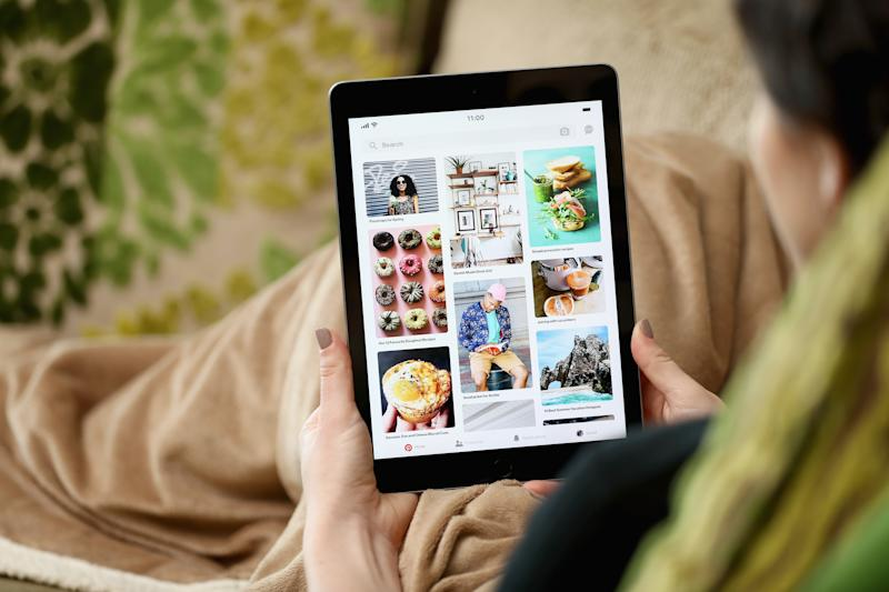 A woman on a couch looks at Pinterest's app on an iPad.