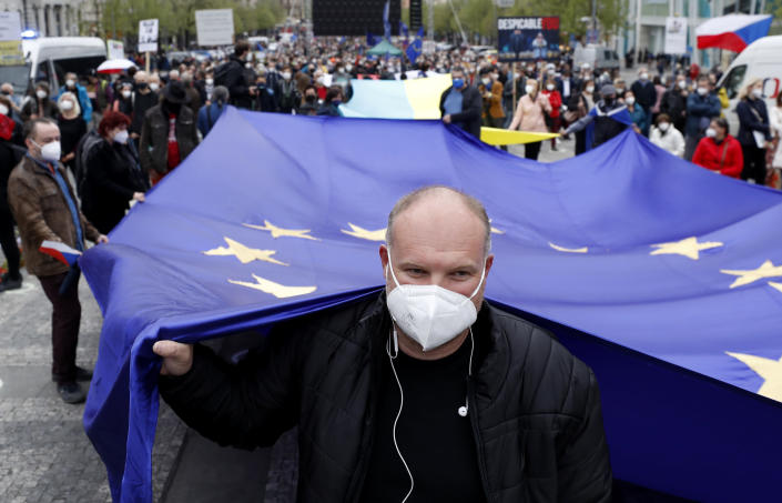 Man holds an EU flag during a demonstration in Prague, Czech Republic, Thursday, April 29, 2021. Thousands of Czechs have rallied in the capital against President Milos Zeman, accusing him of treason for his pro-Russian stance over the alleged participance of Russian spies in a Czech huge ammunition explosion. (AP Photo/Petr David Josek)