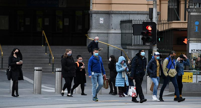 A photo shows people in Melbourne leaving Flinders Street train station wearing masks.