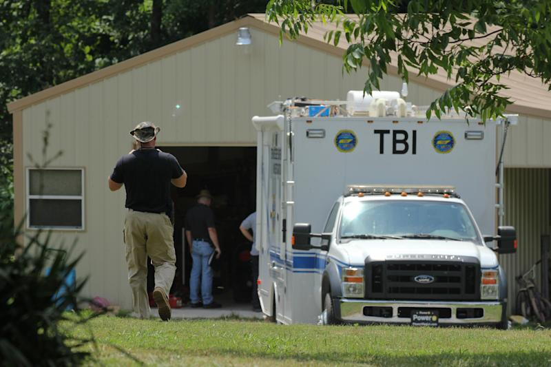 Tennessee Bureau of Investigation agents inspect the home and garage of a woman and her three young daughters who authorities say were abducted near Whiteville, Tenn., on Sunday, May 6, 2012. The FBI has said two bodies were found at a home connected to Adam Mayes in Mississippi, but agents have released few other details. (AP Photo/Erik Schelzig)