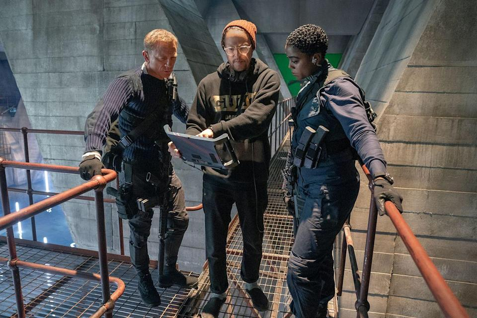 <p>Director Cary Fukunaga stands between Daniel Craig and Lashana Lynch on the set of 'No Time To Die', 2020</p>
