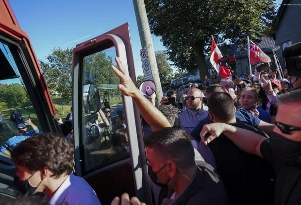 RCMP security detail put their hands up to protect Liberal Leader Justin Trudeau from rocks as protesters shout and throw gravel following a campaign stop in London Ont., on Monday, September 6, 2021. (Nathan Denette/The Canadian Press - image credit)