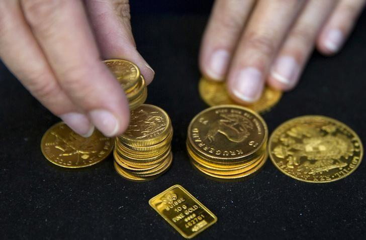 A worker places gold coins on display at Hatton Garden Metals precious metal dealers in London