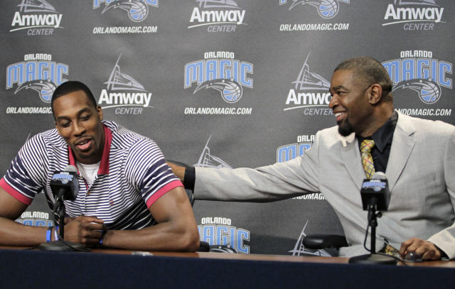 Orlando Magic center Dwight Howard, left, gets a pat on the back from general manager Otis Smith during a news conference,Thursday, March 15, 2012, in Orlando, Fla. Howard signed papers Thursday agreeing to waive the early termination option in his contract, guaranteeing he will be with the Magic at the beginning of the 2012-13 season. (AP Photo/John Raoux)