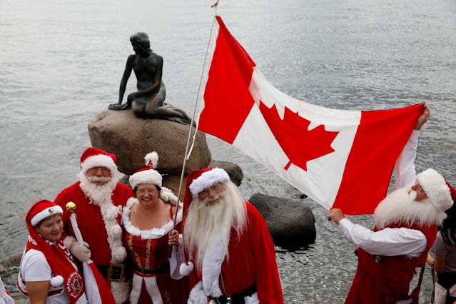 <p>People dressed as Santa Claus, meet at the Little Mermaid statue, as they take part in the World Santa Claus Congress, an annual event held every summer in Copenhagen, Denmark, July 23, 2018. (Photo: Andrew Kelly/Reuters) </p>