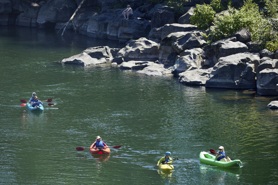Kayakers paddle on the Clackamas River to escape from the heat during a record setting heat wave in Oregon City, Ore., Sunday, June 27, 2021. Yesterday set a record high for the day with more records expected today. (AP Photo/Craig Mitchelldyer)
