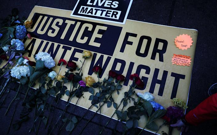Flowers are laid on a sign as protesters rally outside the Brooklyn Center - Reuters