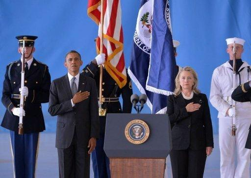 """US President Barack Obama and Secretary of State Hillary Clinton listen to the National Anthem during the transfer of remains ceremony marking the return to the US of the remains of the four Americans killed in an attack this week in Benghazi, Libya, at the Andrews Air Force Base in Maryland. Clinton said their deaths were """"senseless"""" and """"unacceptable."""""""