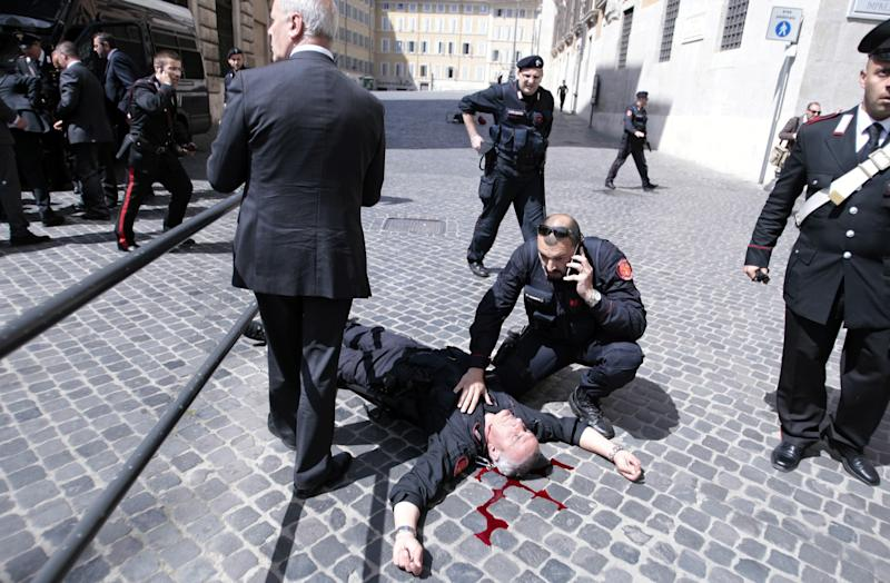 A wounded Carabinieri paramilitary police officer lies on the ground after being shot outside the Chigi Premier's office, in Rome, Sunday, April 28, 2013. Two paramilitary police officers were shot and wounded Sunday in a crowded square outside the Italian premier's office as the new leader Enrico Letta was sworn in about a kilometer (half-mile) away. It was unclear if there was any connection between the events. (AP Photo/Mauro Scrobogna, Lapresse) ITALY OUT