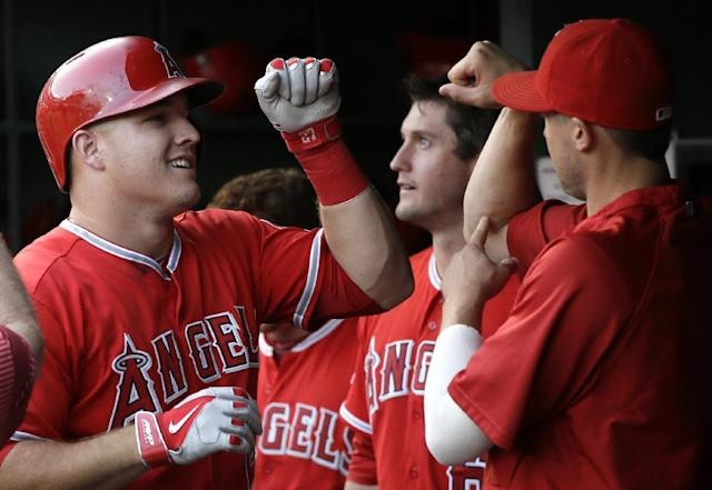 Los Angeles Angels' Mike Trout celebrates in the dugout with teammates after hitting a solo home run off of Texas Rangers starting pitcher Nick Tepesch in the fourth inning of a baseball game, Friday, July 11, 2014, in Arlington, Texas. (AP Photo/Tony Gutierrez)