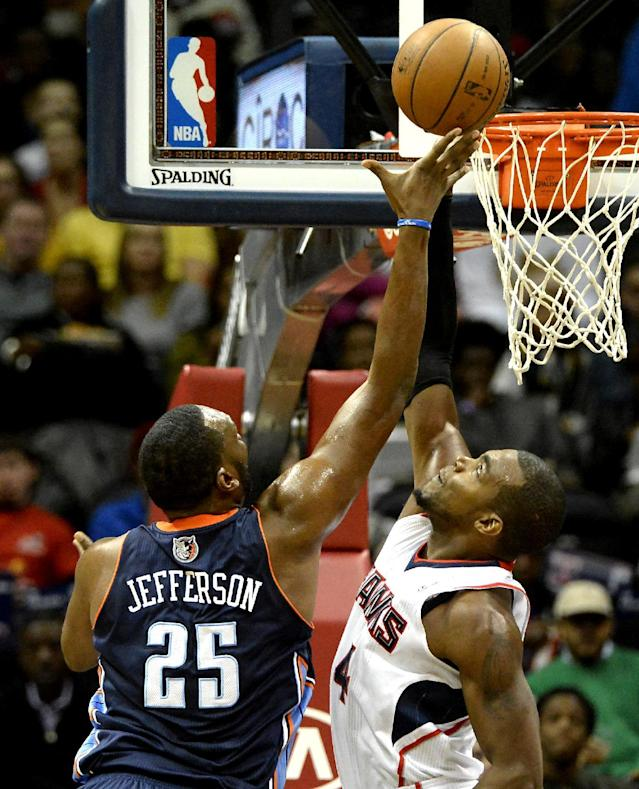 Atlanta Hawks' Paul Millsap (4) blocks Charlotte Bobcats center Al Jefferson (25) in the first half of their NBA basketball game on Saturday, Dec. 28, 2013, in Atlanta. (AP Photo/David Tulis)