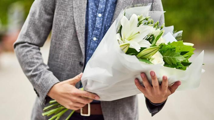 Cropped shot of a man holding a bouquet of flowers.