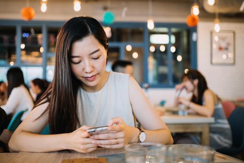 Young woman text messaging on smartphone while waiting for her meal in the restaurant