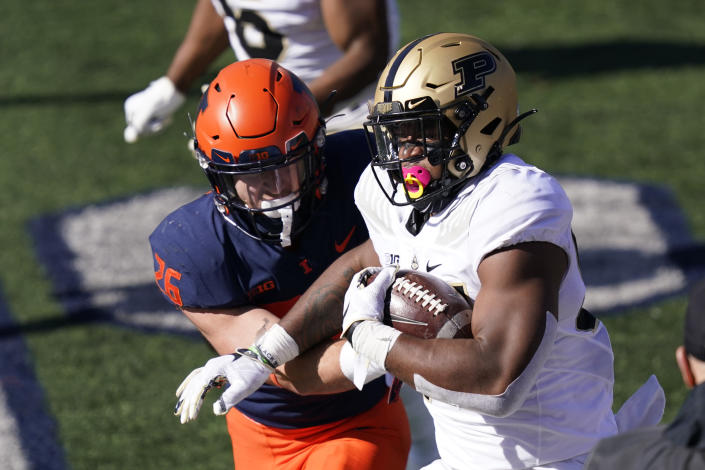 Purdue linebacker Derrick Barnes advances his interception of a pass by Illinois quarterback Coran Taylor, as running back Mike Epstein defends during the first half of an NCAA college football game Saturday, Oct. 31, 2020, in Champaign, Ill. (AP Photo/Charles Rex Arbogast)
