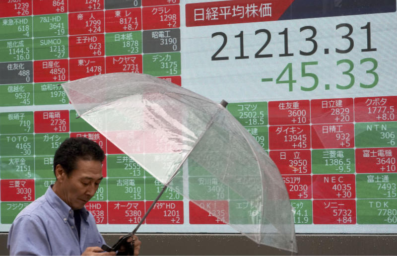 A man walks past an electronic stock board showing Japan's Nikkei 225 index at a securities firm in Tokyo Monday, June 24, 2019. Shares were wavering in Asia on Monday as investors watched for movement in the China-U.S. trade dispute ahead of a meeting between Presidents Donald Trump and Xi Jinping planned for later this week in Osaka, Japan, at the Group of 20 summit. (AP Photo/Eugene Hoshiko)