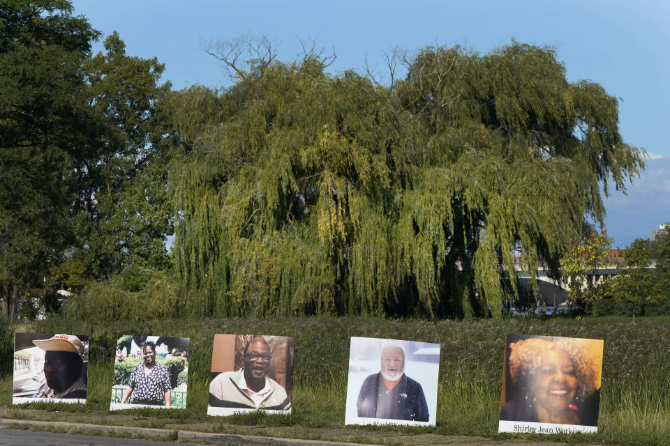A procession of vehicles drive past photos of Detroit victims of COVID-19, Monday, Aug. 31, 2020 on Belle Isle in Detroit. Families have a chance to take one last public look at their lost loved ones in the nation's first citywide memorial to honor victims of the pandemic. Mourners will join 14 consecutive funeral processions to drive past nearly 900 large poster-sized photos of their loved ones staked around the island. (AP Photo/Carlos Osorio)