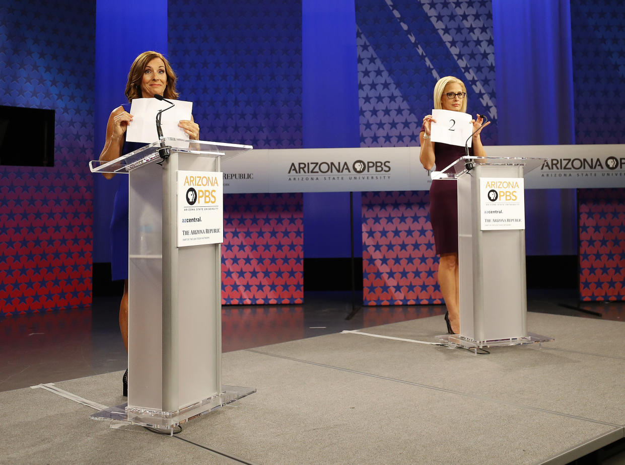 Sinema and McSally hold up signs showing their speaking order prior to a televised debate on Oct. 15, 2018, in Phoenix. (Photo: Matt York/AP)