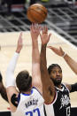 Dallas Mavericks guard Luka Doncic, left, shoots as Los Angeles Clippers guard Paul George defends during the first half in Game 5 of an NBA basketball first-round playoff series Wednesday, June 2, 2021, in Los Angeles. (AP Photo/Mark J. Terrill)