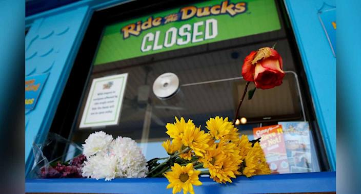 Flowers left by mourners rest on the ticket counter at the closed Ride the Ducks attraction Saturday. Source: AP via AAP