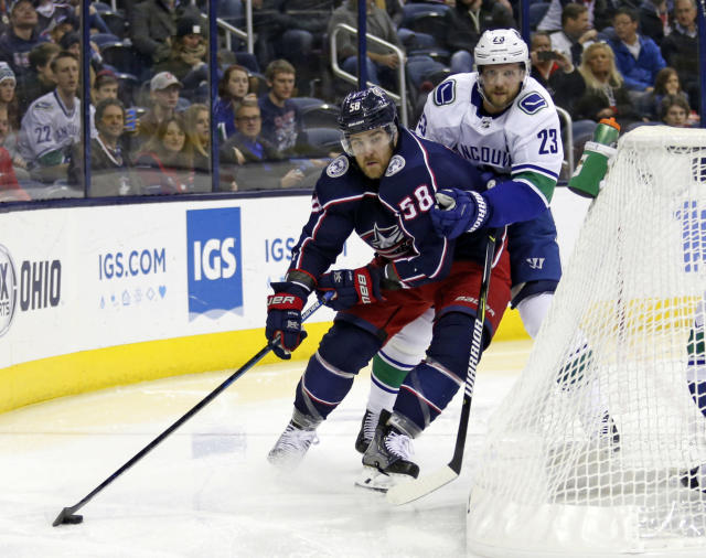 Columbus Blue Jackets defenseman David Savard, left, works against Vancouver Canucks defenseman Alexander Edler, of Sweden, during the second period of an NHL hockey game in Columbus, Ohio, Tuesday, Dec. 11, 2018. (AP Photo/Paul Vernon)