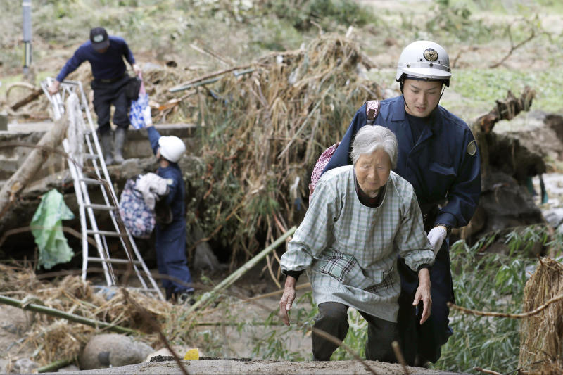 Residents are helped to walk through a road blocked by debris caused by Typhhon Hagibis, to head to a shelter in Koriyama, Fukushima prefecture, Japan Tuesday, Oct. 15, 2019. More victims and more damage have been found in Typhoon Hagibis-hit areas of central and northern Japan, where rescue crews are searching for people still missing. (Kota Endo/Kyodo News via AP)