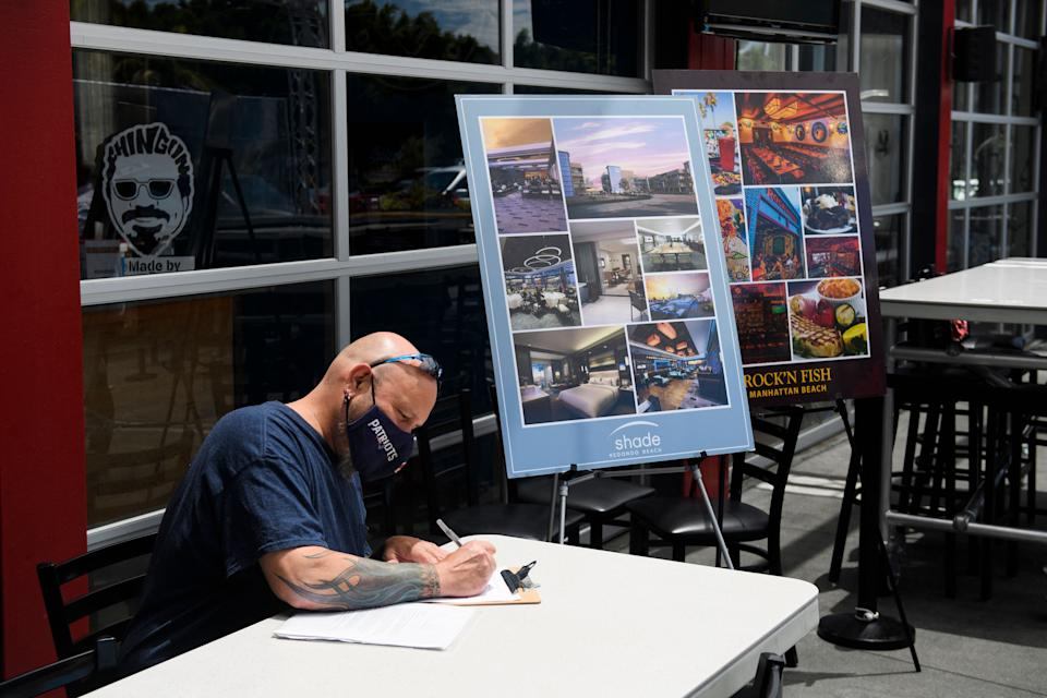 Ray Liberge completes a job application before interviewing and later being hired for a job on the spot as a line cook during a Zislis Group job fair at The Brew Hall on June 23, 2021 in Torrance, California. - Employers at the job fair for Zislis Group boutique hotel and restaurant management company, offered hiring incentives, including a $500 signing bonus and $200 per month for medical benefits after 90 days of employment. (Photo by Patrick T. FALLON / AFP) (Photo by PATRICK T. FALLON/AFP via Getty Images)