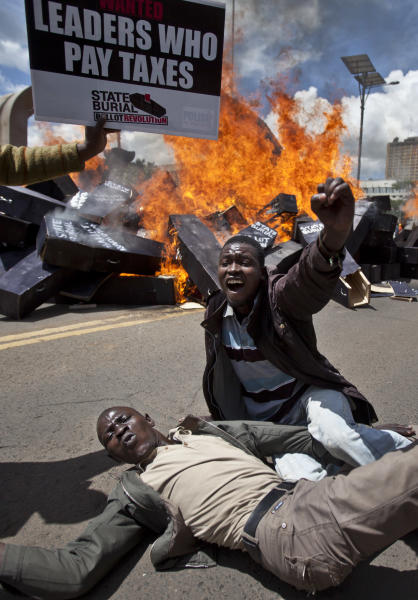 "Demonstrators celebrate after setting fire to mock coffins on which were written ""State Burial, Ballot Revolution"" outside the Parliament in Nairobi, Kenya Wednesday, Jan. 16, 2013. Hundreds of demonstrators angered at outgoing Kenyan legislators, whose term ended earlier this week and who earn about $175,000 a year in a country where the average annual income is $1,700, doused 221 mock coffins with gasoline, one for each legislator, to protest against last week's attempt to award themselves a $110,000 bonus, which was vetoed by the president. (AP Photo/Ben Curtis)"