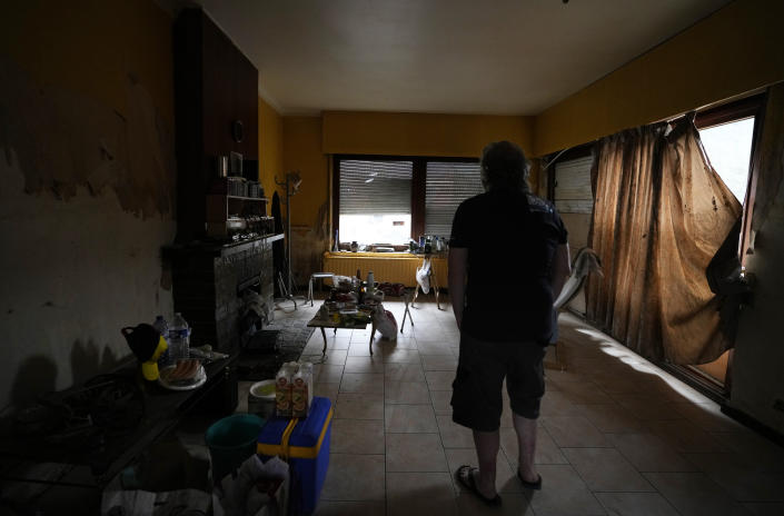 Resident Alan Mereschal stands in what is left of his home after flooding in Vaux-sous-Chevremont, Chaudfontaine, Belgium, Saturday, July 24, 2021. Mereschal, in an effort to help himself psychologically during the flooding, turned to helping others in using his language skills to help translate between residents and rescue personnel. (AP Photo/Virginia Mayo)