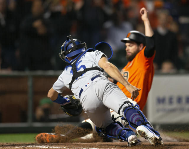 Los Angeles Dodgers catcher Austin Barnes (15) dives too late to tag out San Francisco Giants' Brandon Belt, who scored from second on a single by Kevin Pillar during the sixth inning of a baseball game Friday, June 7, 2019, in San Francisco. (AP Photo/D. Ross Cameron)