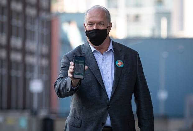 B.C. Premier John Horgan shows his provincial COVID-19 vaccine card as he arrives for a National Day for Truth and Reconciliation announcement with the B.C. Lions in Vancouver on Sept. 16. Horgan is the current chair of the Council of the Federation. (Darryl Dyck/The Canadian Press - image credit)