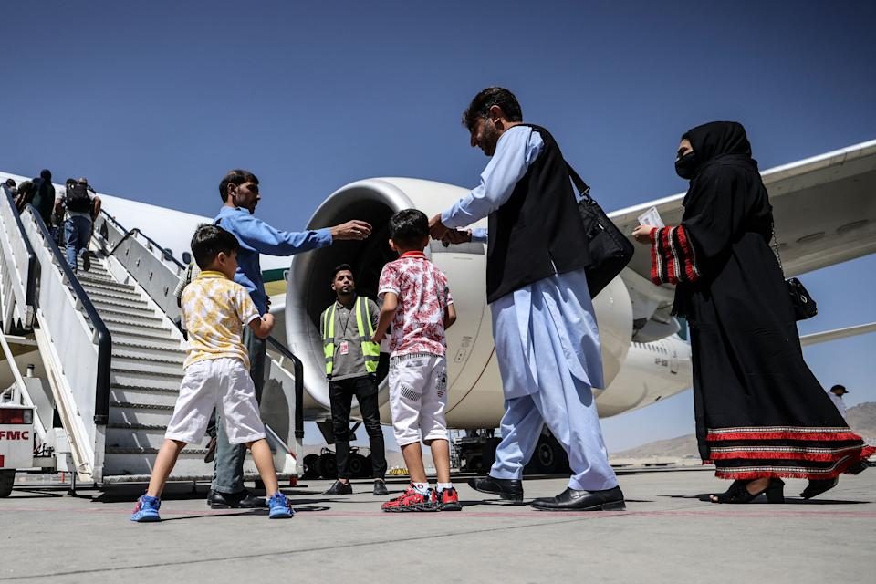 At the airport in Kabul on Sept. 13, passengers wait to board a Pakistan International Airlines plane, the first international commercial flight to land since the Taliban retook power in Afghanistan on Aug. 15.