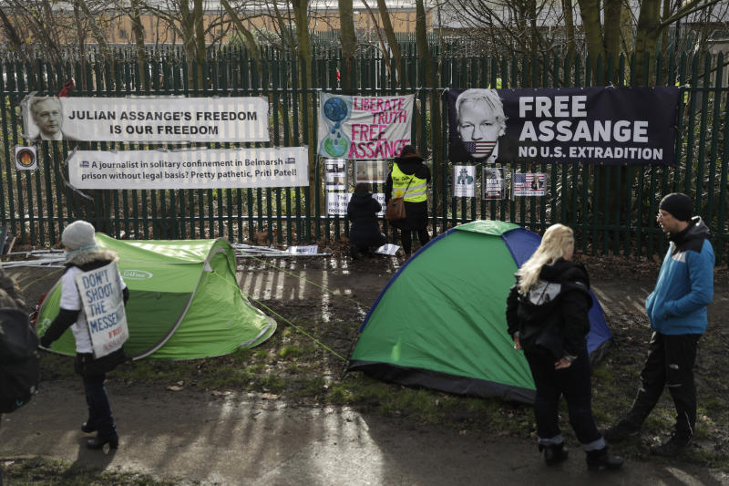 "Supporters of Julian Assange tape up protest messages on a fence by supporters' tents on the second day of a week of opening arguments for the extradition of Wikileaks founder Julian Assange outside Belmarsh Magistrates' Court in south east London, Tuesday, Feb. 25, 2020. U.S. authorities, want to try Assange on espionage charges. A lawyer for the Americans said the Australian computer expert was an ""ordinary"" criminal whose publication of hundreds of thousands of secret military documents put many people at risk of torture and death. (AP Photo/Matt Dunham)"